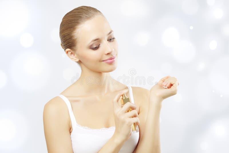 Jong vrouwen bespuitend parfum royalty-vrije stock foto's