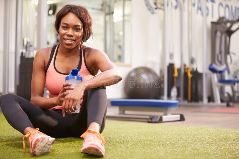 Jong vrouwen drinkwater in een gymnastiek, met exemplaarruimte royalty-vrije stock foto's