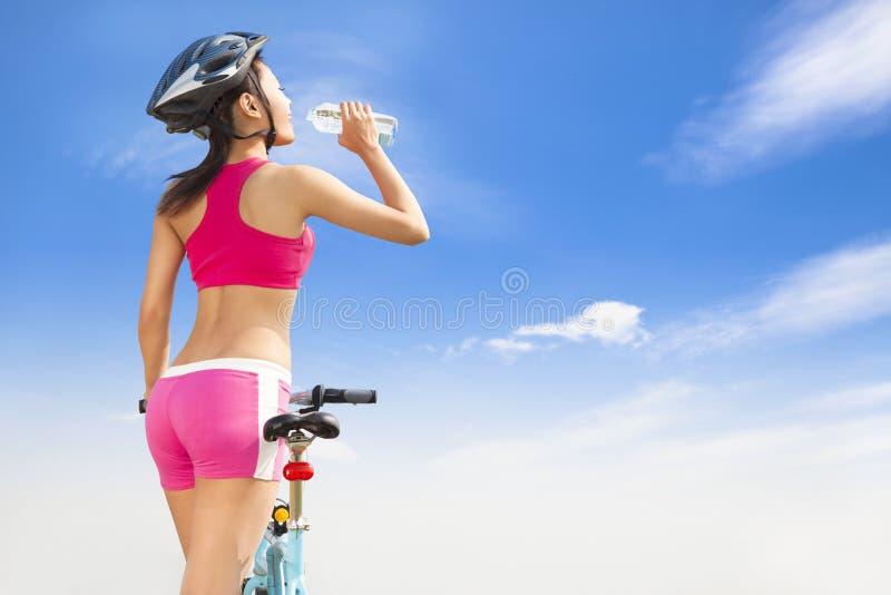 Jong vrouwen drinkwater met het vouwen van fiets stock afbeelding