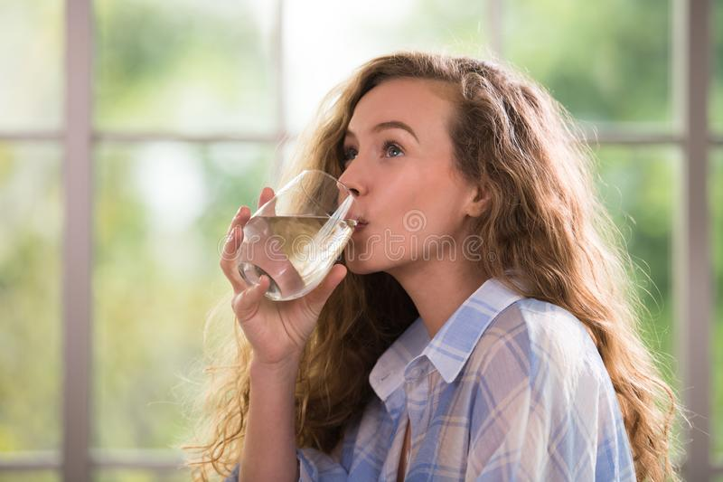 Jong vrouwen drinkwater thuis stock foto