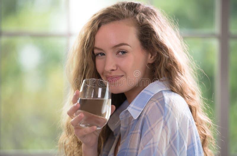 Jong vrouwen drinkwater thuis stock afbeelding