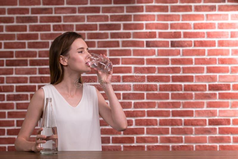 Jong vrouwen drinkwater van glas in de ruimte royalty-vrije stock afbeelding