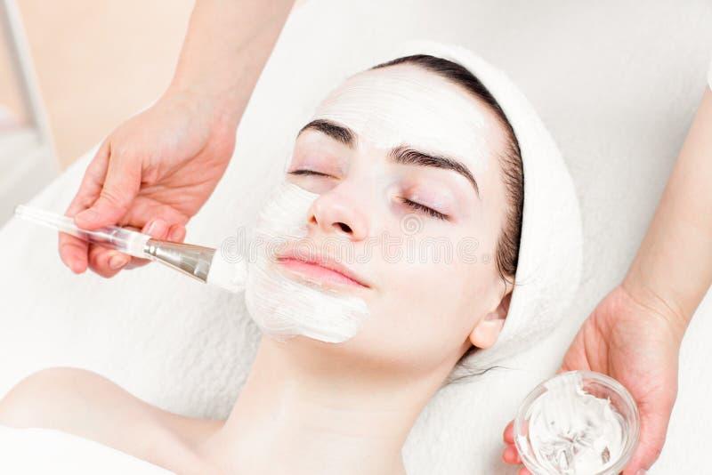 Jong vrouwen gezichtsmasker die in schoonheidswoonkamer van toepassing zijn stock afbeeldingen