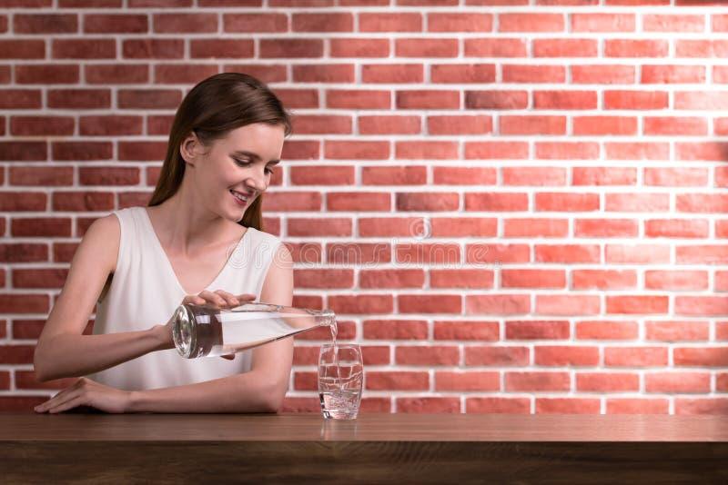 Jong vrouwen gietend water van fles in glas in de ruimte royalty-vrije stock foto's