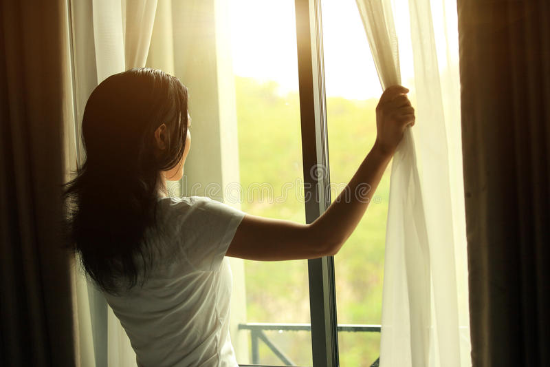 Jong vrouwen open venster royalty-vrije stock foto's