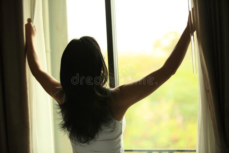 Jong vrouwen open venster stock afbeelding
