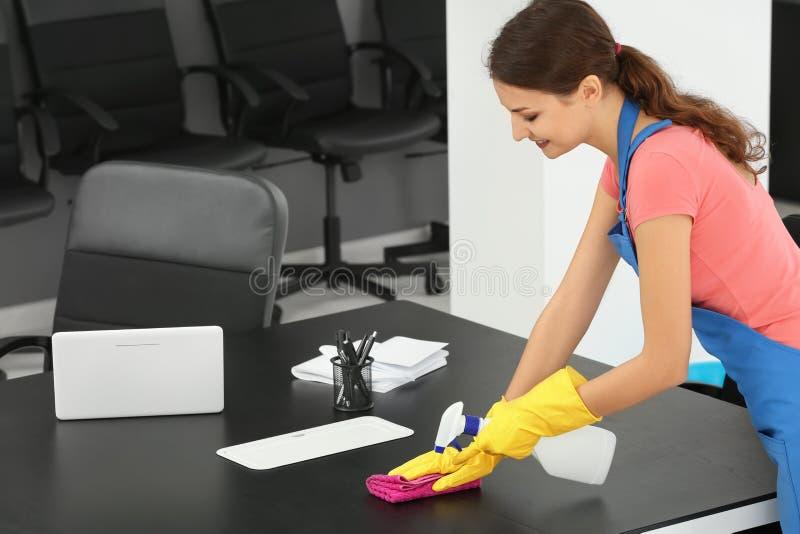 Jong vrouwen schoonmakend bureau stock foto