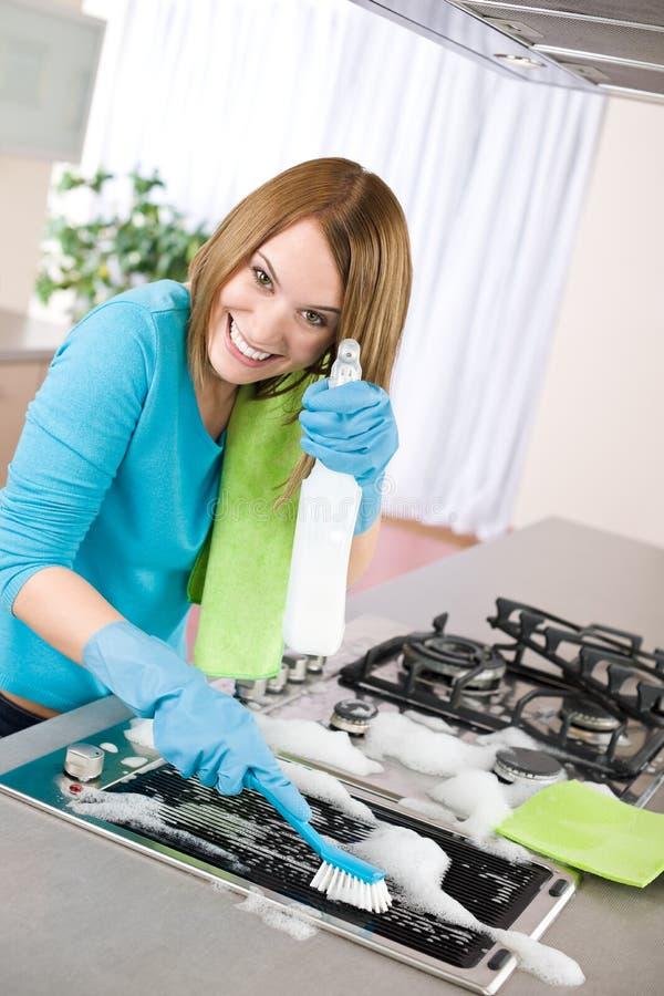 Jong vrouwen schoonmakend fornuis in keuken stock afbeeldingen