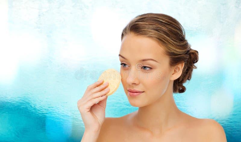 Jong vrouwen schoonmakend gezicht met het exfoliating van spons stock afbeelding