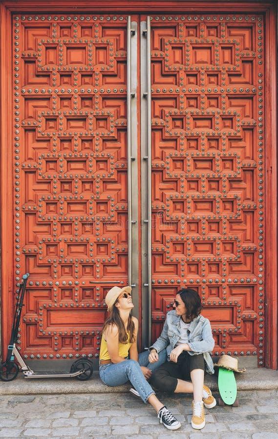 Jong vrouwen vrolijk paar die en elkaar op een rode deurachtergrond kijken glimlachen Zelfde geslachtsgeluk en blij concept stock foto's