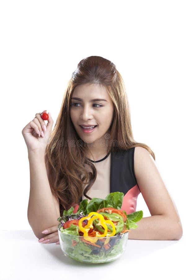 Jong vrouwenbrunette die aanwezig en salade eten stock foto