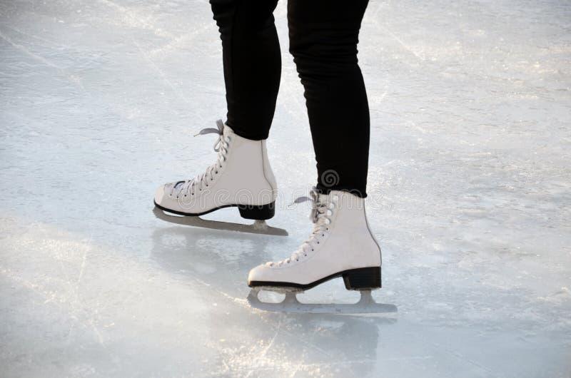 Jong vrouwenijs die in openlucht op een vijver op een bevriezende de winterdag schaatsen royalty-vrije stock fotografie