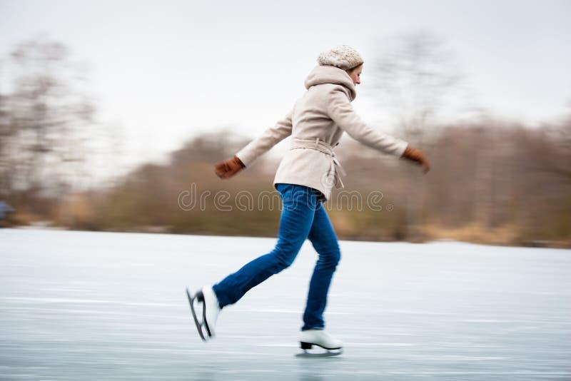 Jong vrouwenijs die in openlucht op een vijver schaatsen royalty-vrije stock afbeeldingen