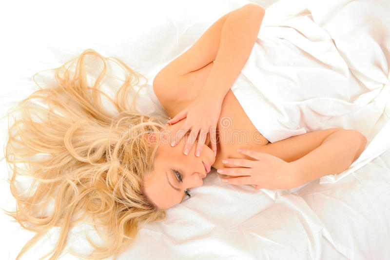 Jong vrouwenportret in bed. royalty-vrije stock afbeelding