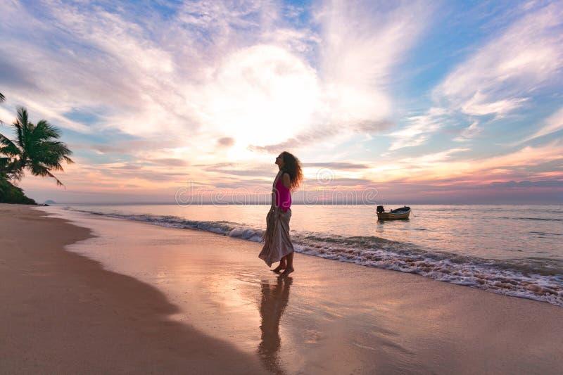 Jong vrouwensilhouet op het strand bij zonsondergang royalty-vrije stock foto's