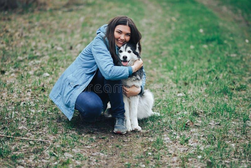 Jong vrouwenspel met schor hond voor een gang in de lentebos die hebbend pret, gelukkig met huisdier lachen stock afbeeldingen