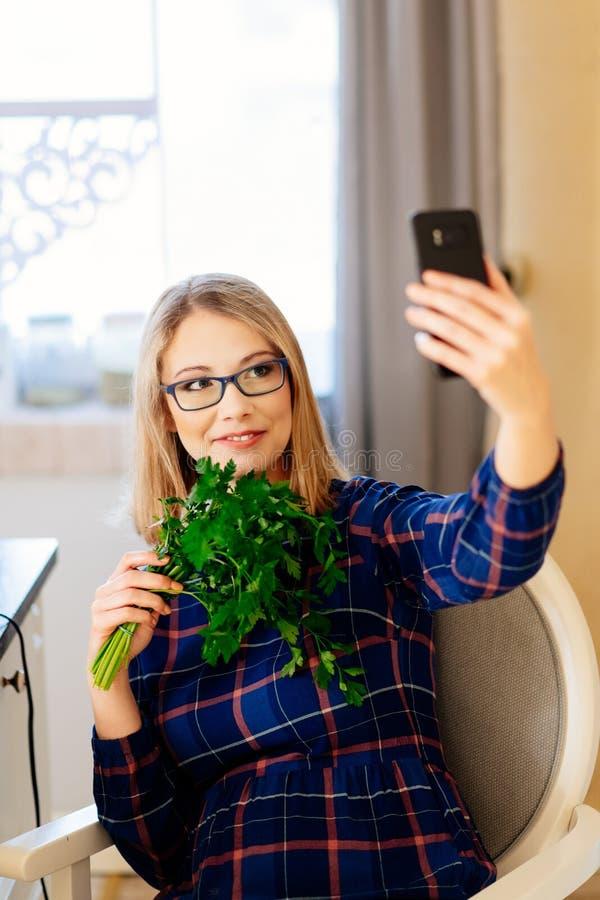 Jong vrouwenvoedsel dat blogger selfie foto met peterselie in keuken neemt stock afbeelding