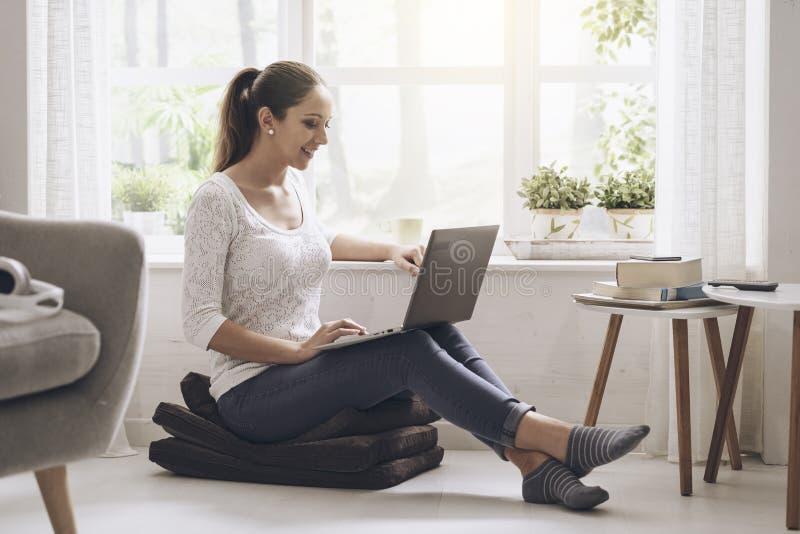 Jong vrouwenvoorzien van een netwerk met haar laptop thuis stock foto's