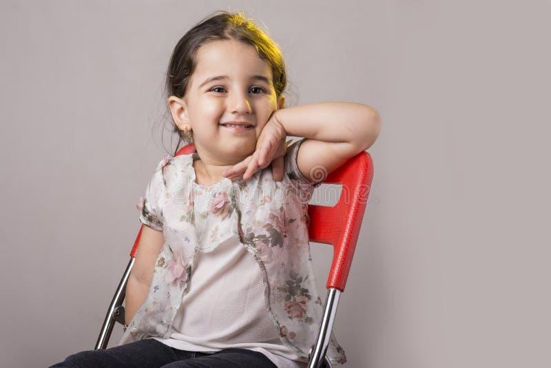 Jong weinig twee van de oude meisjesjaar zetel op een rode stoel voor royalty-vrije stock afbeelding