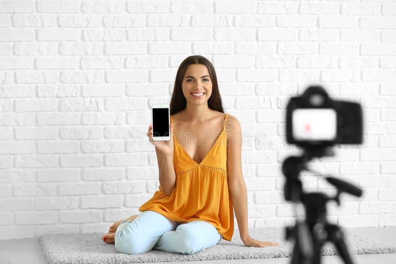Jong wijfje blogger met de mobiele video van de telefoonopname tegen witte bakstenen muur stock fotografie