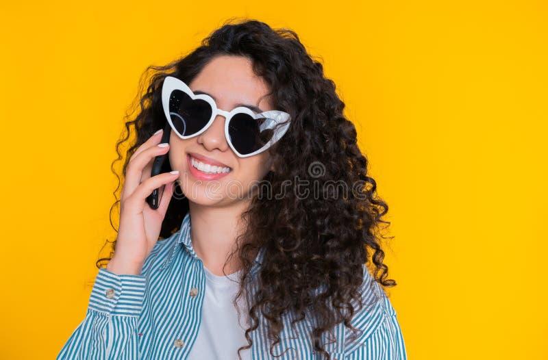 Jong wijfje dat en op mobiele telefoon over gele achtergrond glimlacht spreekt Het mooie gemengde rasmeisje holding en gebruiken stock afbeelding