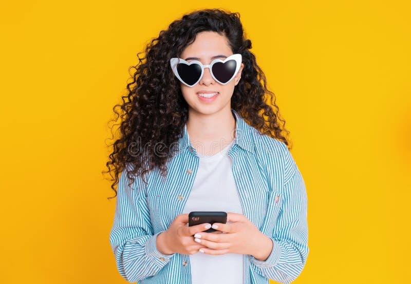 Jong wijfje die en mobiele telefoon over gele achtergrond glimlachen met behulp van De mooie gemengde holding van het rasmeisje e stock fotografie