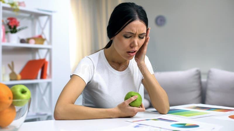 Jong wijfje die freelancer aan tandpijn lijden die groene appel, ontsteking houden stock fotografie