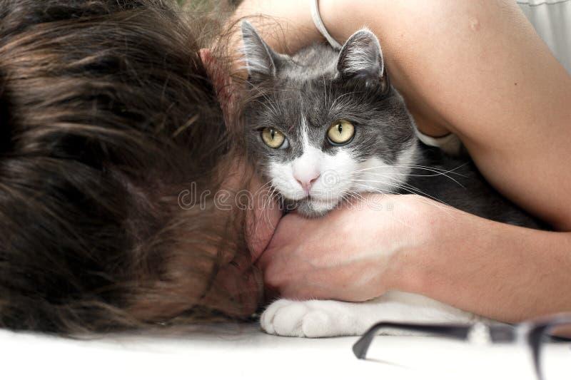 Jong wijfje die haar kat omhelzen stock afbeelding