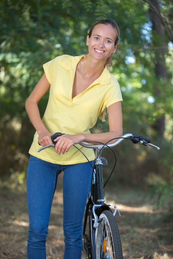 Jong wijfje die met fiets in bos wandelen stock afbeelding