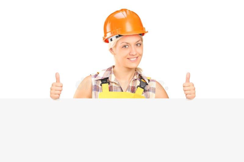 Jong wijfje met helm het stellen achter een paneel met omhoog duimen royalty-vrije stock foto
