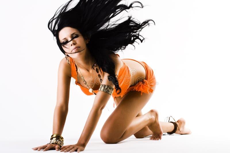Jong wijfje in sinaasappel die lang haar flicking royalty-vrije stock fotografie