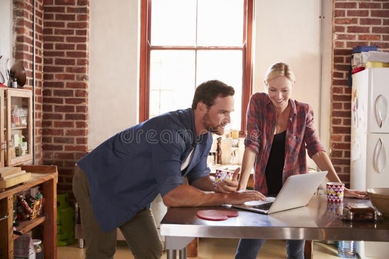 Jong wit paar die laptop computer in hun keuken met behulp van stock afbeelding