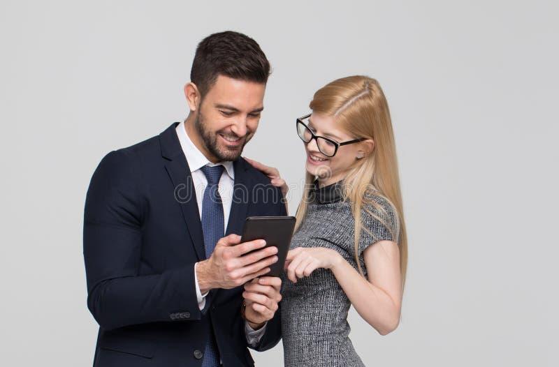 Jong zakenlui die tablet op grijze backgounrd gebruiken royalty-vrije stock afbeelding