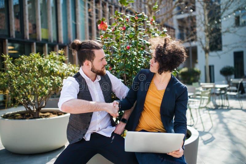Jong zakenlui met laptop in openlucht in binnenplaats, het schudden handen stock afbeelding