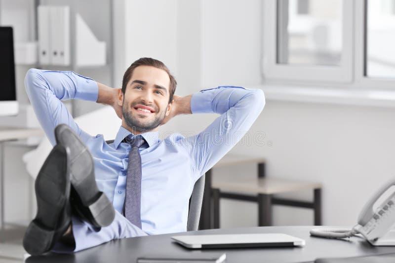 Jong zakenman het ontspannen bureau stock afbeelding