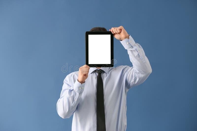 Jong zakenman verbergend gezicht achter tabletcomputer op kleurenachtergrond stock afbeeldingen