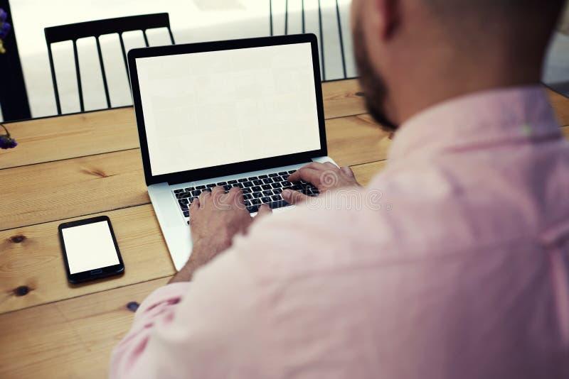 Jong zeker hoofd van de afdelingszitting in het bureau van laptop stock foto