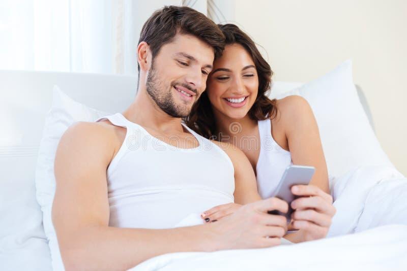 Jong zoet paar die in bed een mobiele telefoon bekijken royalty-vrije stock foto's