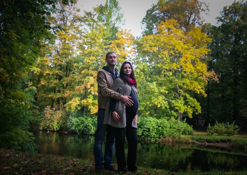Jong zwanger paar in een park in de herfst stock afbeeldingen