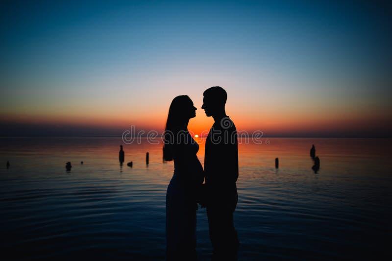 Jong zwanger paar in liefde bij zonsondergang stock foto's