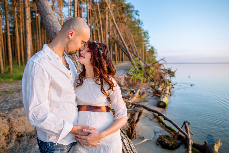 Jong zwanger paar in liefde op de zomer zonnige avond stock foto