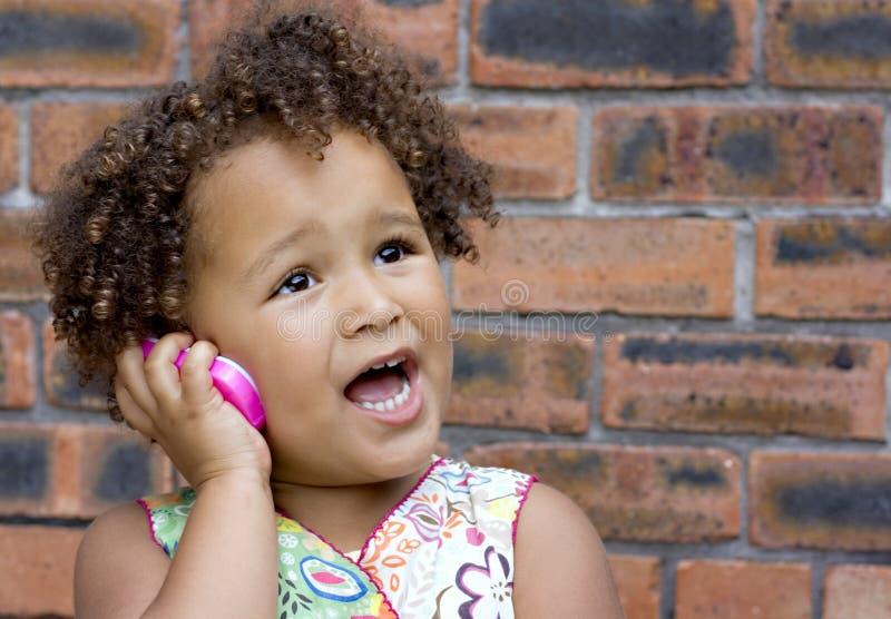Jong zwart babymeisje op een stuk speelgoed celtelefoon stock afbeelding