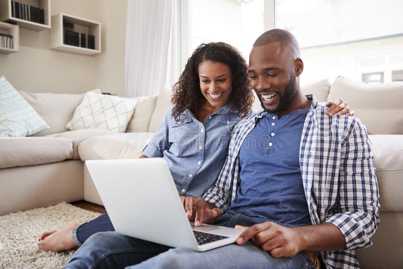Jong zwart paar die laptop zitting op de vloer thuis gebruiken royalty-vrije stock fotografie
