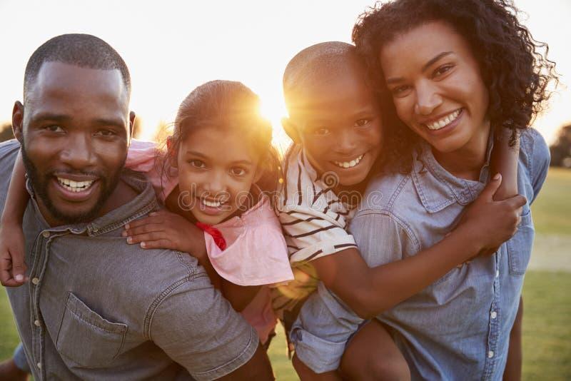 Jong zwart paar met kinderen op vervoer per kangoeroewagen royalty-vrije stock fotografie