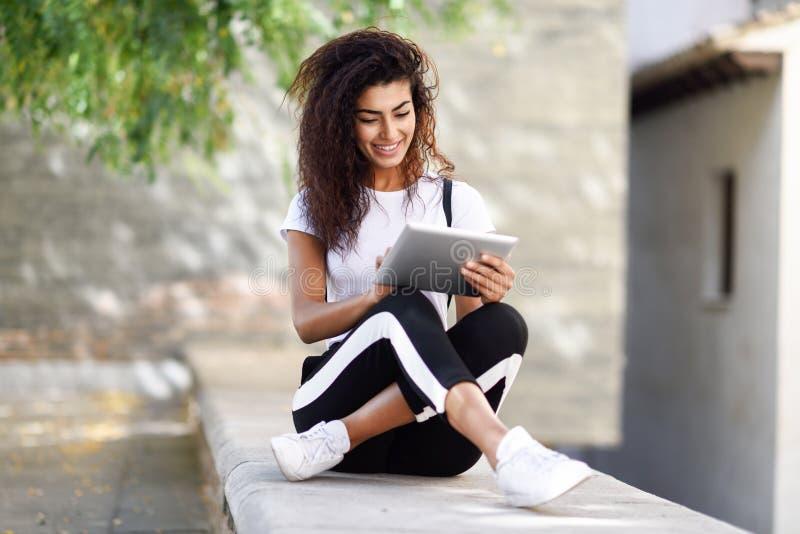 Jong zwarte in sportkleding die digitale tablet in openlucht gebruiken royalty-vrije stock afbeelding