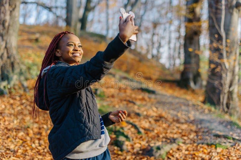 Jonge aanbiddelijke Afrikaanse vrouw met lang haar en mooie glimlach die selfie op de mobiele telefoon in het de herfstpark nemen stock foto