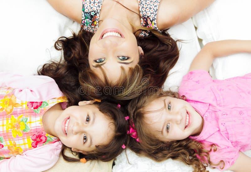 Jonge aanbiddelijke Spaanse zusters met moeder het liggen royalty-vrije stock foto