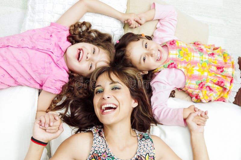 Jonge aanbiddelijke Spaanse zusters met moeder het liggen stock afbeelding