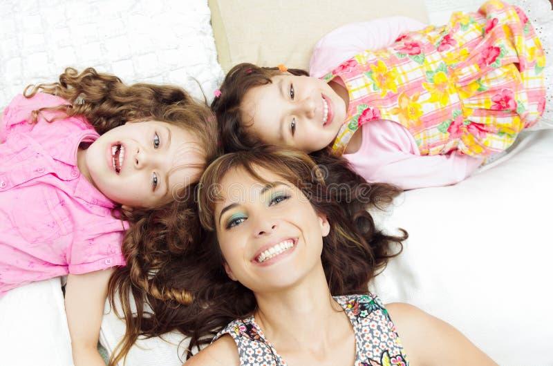 Jonge aanbiddelijke Spaanse zusters met moeder het liggen royalty-vrije stock foto's