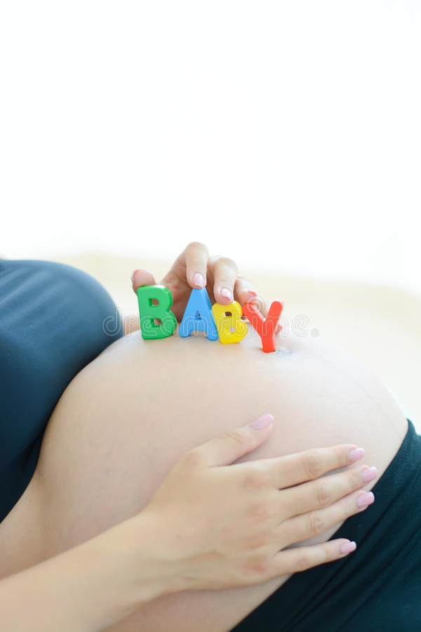 Jonge aanstaande moeder die met brievenblokken baby op haar buik spellen stock fotografie